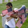 Approximately 200 volunteers prepare for the Memorial Day observance placing some of the 43,00 American flags at gravestones in the Santa Fe National Cemetery in Santa Fe, New Mexico on Friday, May 23, 2014. Clyde Mueller/The New Mexican