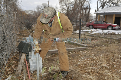 New Mexico National Guardsman, Albuquerque city police and employees of Zia Natural Gas Company of Ruidoso, New Mexico were among hundreds of volunteers who helped turn on gas meters and check pilot lights so they could restore heat to the homes of thousands of northern New Mexicans on Monday, February 8, 2011.  Clyde Mueller/The New Mexican