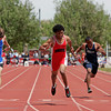 Robertson's Estevan Vigil, center, stretches as he crosses the finish line first during his 100 meter dash at the 2010 State Track and Field Championships at Great Friends of UNM Track Complex on May 8, 2010.               Luis Sanchez Saturno/ The New Mexican.