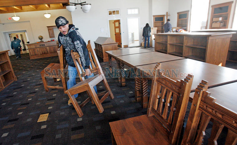 Jose Luevano, from Albuquerque, with Ernest Thompson Furniture, works on bringing the new chairs into the new library at Carlos Gilbert Elementary School on Jan. 4, 2010. The staff has begun moving back in to the school which has been closed for more than a year for major renovation of the downtown elementary school.           Luis Sanchez Saturno/ The New Mexican
