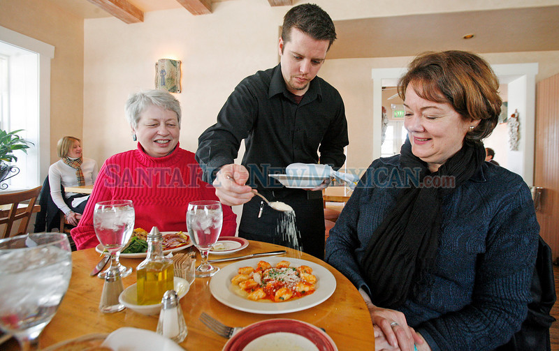 Pat Anker, left, from Santa Fe, watches as server Calvin Lathrop sprinkles Parmesan cheese on Teresa Altemeyer's lunch at Osteria on Feb. 23, 2010.  Luis Sanchez Saturno/The New Mexican.