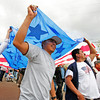 (l-r) Mauro Perez and Bernarndo Miramoto help carry a large American flag as they march through the streets of Santa Fe, N.M. on May 1, 2010, joining a protest against Arizona's new immigration law.<br /> Natalie Guillén/The New Mexican