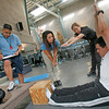 Fidel Cordova, left, recruiting officer, Stephanie Rivera, center, recruiting officer, and Sgt. Gillian Alessio, right, help Ilisandro de Mayo, from Santa Fe, take his sit and reach test during the Santa Fe Police Department's physical fitness test for recruits at the Genoveva Chavez Community Center on Oct. 24, 2009. De Mayo did not pass his physical test but he has the opportunity to re-take it within 30 days.        (Luis Sanchez Saturno/The New Mexican)