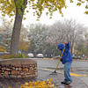 Agustin Gonzalez rakes up fallen leaves in fron of trhe Art & Russia gallery on Canyon Road. Light snowfall greeted Santa Fe residents Wednesday morning. The forecast calls for two to six inches of possible snow fall possible through the day. <br /> Clyde Mueller/The New Mexican