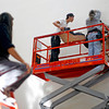 "Artist Roxanne Swentzell, left, watches from a ladder as Cannupa Hanska, center, and husband Tim Star, right, work on installing a public art piece at the Santa Fe Community Convention Center on Nov. 17, 2009. The piece is entittled ""Family: A Statement on Comunity.""          Luis Sanchez Saturno/ The New Mexican"