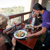 Waiter David Nieto, from Santa Fe, brings out a salad order for costumers Anne Caldwell, left, and Judy Eckhart, back right, at The Museum Hill Cafe on nov. 17, 2009. The cafe will close at the end of November, says Walter Burke who has run the luncheon restaurant amid the cluster of state museums on Santa Fe's east side since it opened in May of 2002.          Luis Sanchez Saturno/ The New Mexican