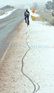 Howard Riley pedals his way to work along a snowy Old Las Vegas Highway Monday morning.  Clyde Mueller/The New Mexican