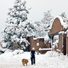 Taking a dog for a walk through 6 inches of new snow along Old Pecos Trail in Santa Fe New Mexico January 19, 2010, Tuesday Morning. <br /> Clyde Mueller/New Mexican