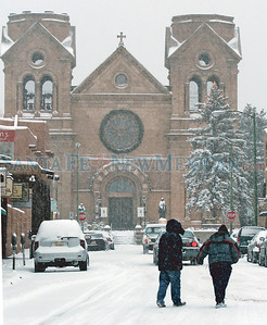 Caption as published: People cross East San Francisco Street near the Cathedral  Basilica of St. Francis of Assisi in December. New Mexico has gotten heavy snows this winter, an unusual but not unheard of occurrence.  Amiran White The New Mexican Raw caption: People make their way across snow cover West San Francisco by the St. Frances Cathedral in Santa Fe, N.M. Dec. 20, 2006 morning.  Amiran White/ The New Mexican