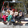 (L-R) Ski Basin employees Laura Houck, Luke Johnson, Braden Anderson and Tyra Dillenschneider (cq) ski the quad without shirts to celebrate the warm weather and last weekend of ski season in Santa Fe, N.M. on April 2, 2011. <br /> Natalie Guillen/The New Mexican