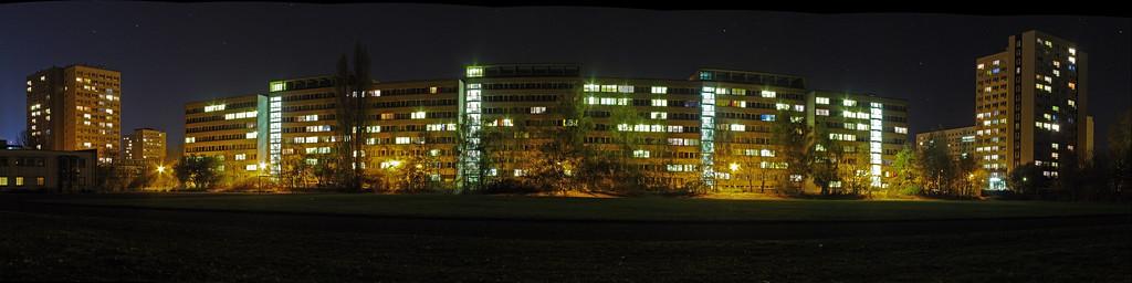 2005-11-05_07098 Wohnheimkomplex in der Tarostraße von der Rückseite vom Sportplatz aus gesehen. Ich hab dort gute 20 Minuten verbracht und über 30 Bilder geschoßen, aber letztendlich doch fast alle wieder gelöscht. Beim Warten auf die Kamera bei den ständigen Langzeitbelichtungen hab ich auch eine Sternschnuppe gesehen! Die Erste in meinem Leben habe ich vor ein paar Wochen gesehen. (Panorama aus 7 Bildern - auf Original klicken für Detailansicht) View on the residence halls in the Tarostraße from behind. I spent over 20 minutes there shooting more than 30 pictures, but I ended up deleting most of them. While waiting for the camera during all these long-time exposures I saw a shooting star! The first one in my life I saw a couple of weeks ago. (panorama out of 7 pictures - click on Original for a detailed view)