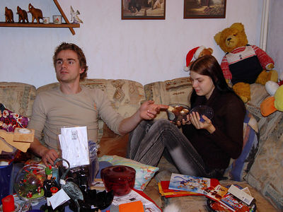 2005-12-24_07801 Die Bescherung findet dieses Jahr ein paar Stunden eher statt. Simone hat eine Tupperdose mit selbstgebackenen Keksen ausgepackt und Thomas präsentiert sie dem Rest der Familie The distribution of Christmas presents takes place a couple of hours earlier this year. Simone has unwrapped a Tupperware box filled with homemade cookies and Thomas presents it to the rest of the family.