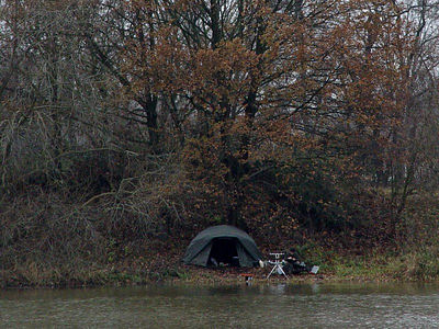 2005-12-09_07601 Ein einsamer Camper mit Angelausrüstung am feucht-kalten Flußufer A lonely camper with his fishing rod sitting at the wet and cold riverbank.