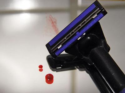 2006-03-15_08996  Heute hab ich mich mal wieder mit einem der billigsten Rasierer, die es hier gibt, rasiert (seit Valentins Tag). Und nein - ich hab mich dabei nicht geschnitten, obwohl dies echtes Blut ist. Das passiert mir nur, wenn ich mich regelmäßig rasiere.Später war ich dann auf der Suche nach einem Tagesbild und dies hier ist mir eingefallen. Das einzige Problem dabei war etwas Blut aufzutreiben ohne dabei die Kamera zu ruinieren. Deshalb hab ichs zuerst mit dem kleinen Finger der linken Hand probiert, der beim fotografieren nicht benötigt wird, aber irgendwie waren die Nadeln aus meinem Notfallnähset nicht dick genug (siehe Blutspur über dem Rasierer). Irgendwann hab ich dann mal mit Hilfe einer Nagelschere etwas Blut aus der Seite meines Zeigefingers herausbekommen. Today I shaved again (since Valentins Day) with the one of the cheapest razors available and no - I didn't cut myself with it even though this is real blood. That only happens when I shave regualry.Later I was searching for a photo idea and came up with this. The only problem was getting some blood without messing up the camera. So I tried the little finger of the left hand which I don't need while photographing, but the needles of my emergency sew kit weren't thick enough (see blood trace above the razor). Eventually I got two little drops using nail scissors at the side of my index finger.