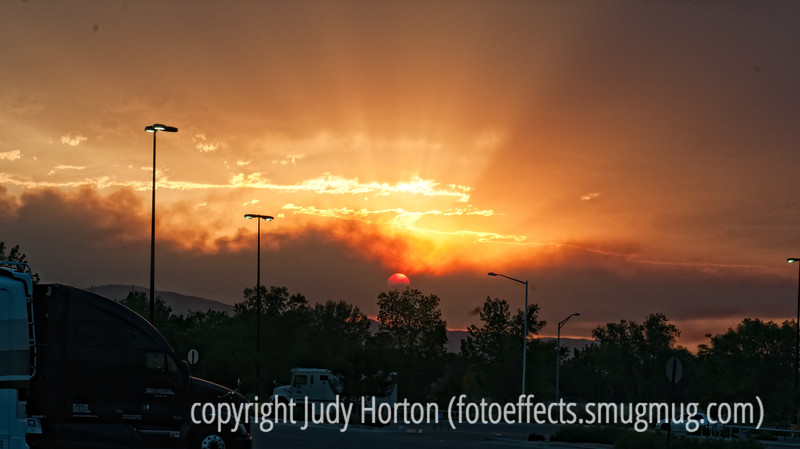 8/16/12 - Smoke from the Hyde Park fire near Ft. Collins makes for a spectacular sunset.  This was taken when we were just starting out for South Dakota, but I just finished the processing of this file yesterday.  We actually were in a Walmart parking lot when I took this shot.  Clearly, this would have been better if I'd been in a better location without so much commercial stuff in the foreground, but, unfortunately, I did not have a chance to do that and had to take my sunset as it came!  Constructive criticism is always welcome.<br /> <br /> Thanks for the comments on my shot of the light trails car.  I thought you all would get a kick out of that.  Hopefully, I'll do it better the next time.