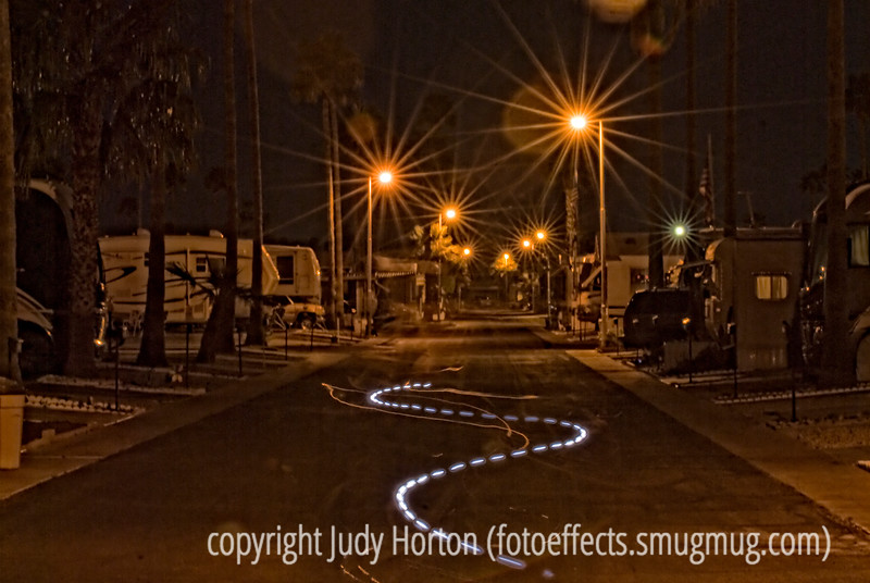 RV Park at Night - I was looking through my recently processed Arizona shots to see if I could find one I'd like to post and I saw this shot that I took in 2009 in Phoenix.  The light trail is from my hubby walking with a flashlight and turning it on and off as I took a long exposure.  It kind of appealed to me tonight, so I decided to post it.<br /> <br /> Thanks for all the encouraging comments on my shot of the great blue herons on the nest.  We had a great hike today up to the Crags.  The only problem was that my hubby took quite a fall and is now really sore and bruised all over.  I got a bunch of shots but none that I'm really crazy about.  Have a great day!