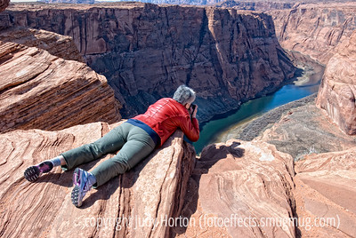 Getting the shot at Horseshoe Bend.  Not my preferred view in which to be photographed.  Since I am the family member who is rarely captured in photos, the reason that I was preserved for posterity in this unflattering position is that I am terrified of heights and, after hiking about 1/2 mile to reach the Horseshoe Bend Overlook, I discovered that the ONLY way to get a shot of the bend in the Colorado River here is to get out to the absolute edge of the sheer cliff dropoff.  No way that I could make myself get out there in a standing position.  Even then, without a fisheye lens, you would not be able to get the whole bend in the picture.  Luckily, I had my fisheye lens.  After walking all around the edge and confirming that they only way I could get a shot of the famous bend was to be on the edge, I lay down and inched myself out so that I could hang my camera over the edge to get some shots.  The shots I got are here: http://fotoeffects.smugmug.com/Landscapes/Northern-Arizona/11896740_iVsC7#842028150_NVySM.  Not fabulous and I'd like to try again on a cloudy day or at sunset.  My hubby, who was holding my other camera, decided to take advantage of me (not for the first time) and took this shot.  I intended to post it right after returning from the trip but other shots kept getting my nod, so I forgot this one until I ran across it this evening in my Northern Arizona gallery.  Hope it gives you a chuckle!  Thanks for the comments on my shot of the milkweed pod and seeds.  Hope your week got off to a good start and that you are finding a few moments to take some shots.