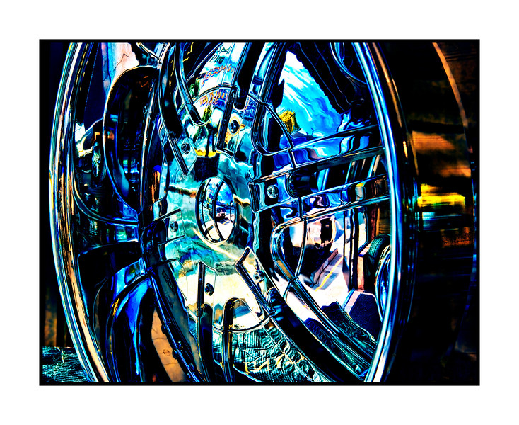 "Reflections in a Chrome Wheel - While waiting for a new windshield to be installed in our little RV, I took a bunch of shots of wheels and car grills at the store next door.  I played around with these shots tonight and this is one of the results.  I put the rest of the shots in my ""Reflections"" gallery (under the category of ""Other"") if you are interested in seeing the others.  Thanks for your responses to my hummingbird shot today.  I was surprised that it was so well received, since it wasn't really what I had been hoping to capture.  However, those little birds are so loaded with personality, it is hard not to warm to them."