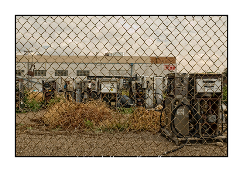 "In the past few weeks as we have been driving to Denver on a regular basis to help our daughter get her pilates studio ready to open, we always drove past this corner lot, fenced, behind which stood a bunch of old, partially dismantled gasoline pumps.  After commenting that I thought there was a photograph opportunity there for several days, we finally stopped one morning and I took some shots.  I've processed them a number of different ways and I'm not sure if I really like any of them or, if so, which one I prefer, but here is one for your critique.  Generally, I don't like shooting anything through a fence, but I think that the fence may actually enhance this image.  It seems kind of odd to bother to fence off these old, rusting and decaying gas pumps, along with a plastic trash can and other detritus.  Anyway, what do you all think?  If you'd care to look at any of the others, they can be found here:  <a href=""http://fotoeffects.smugmug.com/Other/Odds-and-Ends/7032233_9SbQx#636419082_EjsfK"">http://fotoeffects.smugmug.com/Other/Odds-and-Ends/7032233_9SbQx#636419082_EjsfK</a>.  They are on two pages, so you have to look at the next page, as well, to see them all.<br /> <br /> Thanks so much for the nice comments on my hollyhocks pic. And have a great day!  I'm especially thinking about Miguel as he learns more about his cancer and the treatment options."