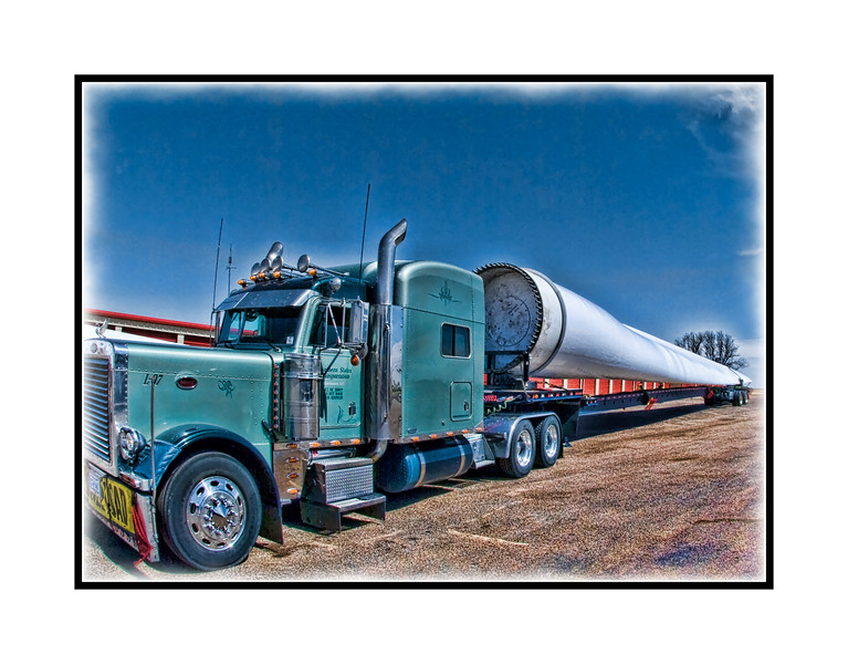 This is a blade for one of the huge wind turbines.  These have three of these blades, each weighing about 18,000 pounds and with a length of about 200 feet.  They are made by an Indian company, Suzlan.  The truck driver said they were delivering the blades to a John Deere wind farm near Gruber, TX in the panhandle near the OK border.  We actually saw three trucks, each carrying one blade.  When we initially saw the trucks, we were filling up our gas tank in  a little Texas town.  We decided to chase them down, pass all of them, get about ten minutes ahead and I would jump out with my camera and tripod and set up on the side of the road to capture them when they came along.  Just after we passed the third truck, Phil saw all of them pull off the side of the road and stop.  We made a quick U-turn and high-tailed it back to where they were stopped.  I got out and asked permission to shoot their truck and load.  When you see these things, you can hardly believe what you are seeing.  I took the pictures with a fish eye lens, since these things are soooo long.  I'm going to post this and hit the hay.  Thanks to all of you who commented on my roadrunner pic.  I sure enjoyed everybody else's shots today.  I have to say my favorite was Jennifer's shot of Emily leaping in the air.  Have a great day, everyone!