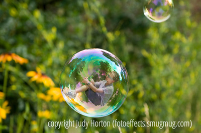 """""""The Boy in the Bubble"""" - song by Paul Simon.  This is the redone version of this.  I took a new photo of a bubble and, instead of cutting out the bubble and putting it on a different background, this time I kept the bubble and the background intact.  All I did was add the boy.  If you look at it in the largest sizes, you'll see the reflections in the bubble now reflect the actual setting in which it was taken --- although you'll see the pine trees in my garden, which do not actually show in the background itself.  You can also see that there are reflections both in front of and behind the boy.  Having done all that, I'm not sure this is really that great an image.  The boy does not pop out at you.  You have to look carefully for him.  However, I think this may be about as good a job as I can do on this idea.  I'd appreciate your thoughts regarding whether I  should enter this or the great balls of fire shot that I posted on the dailies two days ago.  Thanks, as always, for your comments, which I value a lot.  I did learn quite a bit doing this little project and that, of course, is never wasted effort.  Have a great day everyone!  My hubby and I are going up to Denver to help our daughter put up drywall in her new ballet studio."""