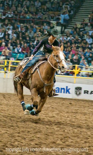 """This young lady was competing in the barrels competition at the rodeo.  Once a horse and rider have gone around each of the barrels, they high-tail it back to the starting line.  It is amazing how fast they go.  This shot captures the speed of that last part of the ride, I think.  Best viewed in the larger sizes.<br /> <br /> I'm so grateful for all the nice responses to my shot of the calf roping, as well as the suggestions for taking better shots of such events in the future.  I did take a few shots at higher shutter speeds, such as 1/400 sec. and, although they were sharper, they also seemed to be darker.  They had spotlights on the arena, but it was still a relatively dark setting in which to capture such rapid action.  An outdoor rodeo would provide much better photographic conditions, I think.  I've processed a bunch more shots, although I still have a lot more to go and they are in a new gallery, """"Rodeo Shots.""""  It snowed here a tiny bit today but we still aren't getting much in the way of precipitation.  Hope your week is going well."""