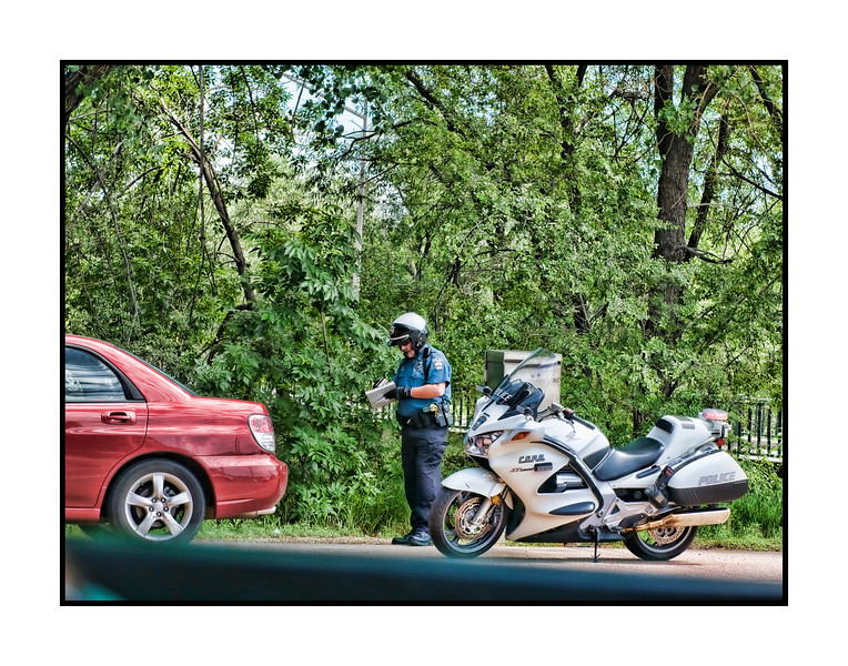 A policeman writing a ticket for speeding. Hope this does not happen to any of you this weekend.  I snapped this shot a couple of days ago on my way to Pilates class.  We're going to the Cherry Creek Arts Festival today --- it is a wonderful arts and crafts outdoor festival.  Lots of the top artists in the country will be there.  There are always a lot of great photographers represented.  It should be lots of fun and is always interesting.  I'll be carrying my camera, of course, hoping for photo ops.  Rain is predicted and since it has been raining every day, it probably will rain on our parade at some point.  Have a great 4th of July!