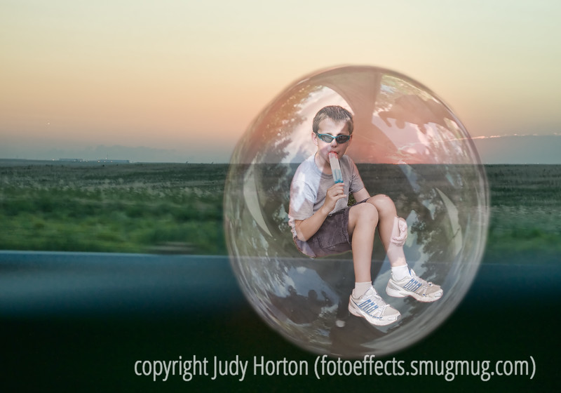 """The Boy in the Bubble"" - song written by Paul Simon and Forere Motioheloa.  The image was created from three separate shots, one of a bubble, one of the boy, and one of the sunrise from the freeway.  This is another image that I created with the Dgrin Challenge in mind.  I certainly appreciate all the suggestions for improving my ""Time in a Bottle"" image.  If you have thoughts on how this one could be improved, as well, I'd love to hear them."