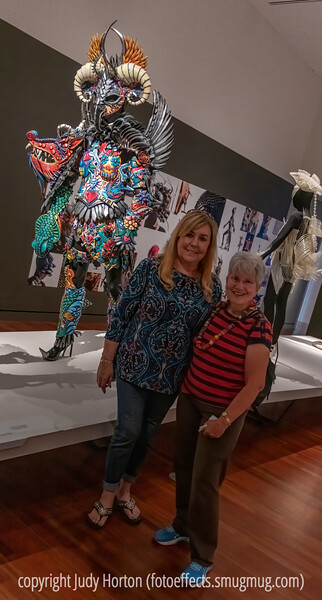 "Linda Good and I in front of one of the World of Wearable Art ""garments"" in the Colorado Springs Fine Arts Center.  This garment is made of EVA foam, painted, sculpted and shaped with heat.  The images on the garment were inspired by the tatoos of the indigenous people of the South Pacific."
