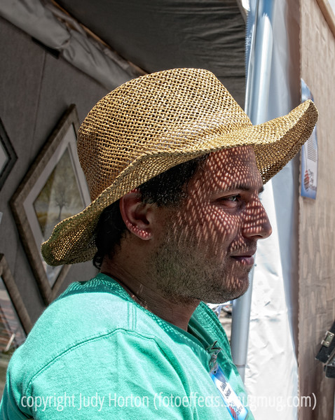 A straw hat casts lacy shadows on the face of a young man at the Cherry Creek Art Festival