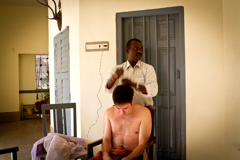 """Head Pounding?, Hazaribagh India<br /> <br /> Nini took this photo of me getting a head and upper body massage after a haircut and shave from her family's barber.  This part of the massage involves hitting the head with fists.  It doesn't sound appealing, but it was actually very relaxing.<br /> <br /> After the massage we had to drive 3 hours to the closest airport to pick up our """"lost"""" luggage, and then drive back to Hazaribagh.  Air France is going to get a real you know what chewing when I get back to the states!  Meanwhile, the Indian airlines have been flawless so far.<br /> <br /> Daily photo: Dec 28, 2011, taken Dec 28, 2011"""