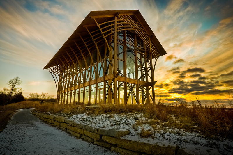 """Holy Family Sunset, Gretna Nebraska<br /> <br /> My little sister Taylor and I went out to take some sunset photos at the Holy Family Shrine about 20 minutes outside of Omaha.  The chapel is a stunning combination of glass and wood.  We see the shrine every time we go to Lincoln, as it's clearly visible from the interstate.  Hopefully we'll go back soon.  For those interested, the Holy Family Shrine website is here: <a href=""""http://www.holyfamilyshrineproject.com/"""">http://www.holyfamilyshrineproject.com/</a><br /> <br /> This is a seven exposure HDR.  So much for my non-HDR streak of two dailies.  This photo caused all kinds of problems in tonemapping and was a big hassle to process.  Even after working on it for a few hours I'm still not satisfied.  I'll have to come back to it on a rainy day.  I had a blast processing and listening to hard core rap music with my dad into the wee hours of the night while everyone in the family was sleeping.  Dad wasn't as into the music as me, but he played along.  Ah the holidays...<br /> <br /> Daily photo: Dec 23, 2011, taken Dec 22, 2011"""