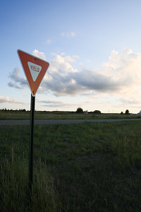 Yield Sign on Country Road at Sunset with Wind Generator in Background