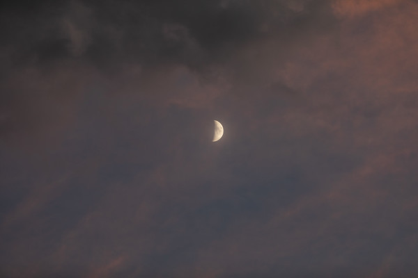 Photo of a Waxing Crescent Half Moon in the Clouds