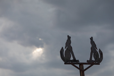 Close up shot of Two Metal Wolves Howling with Clouds in the Background