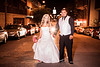 """In the Streets, Columbia MO  Here's the beautiful bride and groom in the middle of my favorite street in Columbia, 8th street.  Jesse Hall, <a href=""""http://smu.gs/N5Pzo8"""">the centerpiece</a> of Mizzou's campus is in the background and the marquee of the historic <a href=""""http://smu.gs/Hgqcd3"""">Tiger Hotel</a> is on the right.  We were all very tired after a long shoot, but Megan and Eric never gave up their smiles.  What an awesome pair!  We waited in the middle of the road for what seemed like 5 minutes until a car finally came our way.  The car was very polite and stopped a ways back and turned off their lights so they wouldn't bother us!  That's Midwest hospitality for you!  I had to shout to get them to turn their lights back on, and we got this shot soon after.    This was shot at f/2, 1/60th of a second, ISO 1600, with a Yongnuo YN 560 speedlite at half power, shot through small diffuser.  Jay held the speedlite a few feet in front of me.  It takes some practice to learn how to balance artificial and ambient light.  If I had turned the speedlite up to full power and got it closer to the subject, then I could have used a smaller aperture, faster shutter, and lower ISO, producing a sharper image of the couple.  But doing so would have significantly darkened the environment around the couple, creating a very bizarre looking image where the couple appears in the middle of a very under-exposed background.  The key is to get the exposure you want of the surrounding environment, and then adding flash to accent the main subject.  In this case I needed ISO 1600 to get the exposure I wanted down 8th street.  Daily photo: August 6, 2012, taken July 28, 2012"""