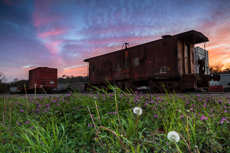 "Colorful Caboose, Nacogdoches TX  Well the caboose isn't really colorful, but the sky is!  I knew from the looks of the clouds in this sky that we were in for a very colorful sunset, but I didn't have time to go to any of our normal sunset locations (aka, the lake).  The railroad tracks are only a few minutes from our house, so I gave it a try.  I'm glad I did because even the ugly old train tracks looked pretty with this sky!  This is a single 4 second exposure.  I used a three-stop soft-step graduated neutral density filter and a two-stop soft-step graduated neutral density filter to balance the exposure between the foreground and the sky.  I wish I had closed down to f/22 for a little added depth of field so that the caboose was in sharper focus.  Focusing on something a little further away would have helped too.  With shots like this, my thinking is that if something is out of focus in the foreground, it is going to be more noticeable than something in the background.  It's for photos like this that I would like to be able to manually blend exposures in photoshop.  That way I could blend one exposure focused on the foreground and another focused on the background, a technique called focus stacking.  But I'd have to get photoshop first!  Thanks for your comments last week!  My most popular photo from last week was very special for me because it is a photo of <a href=""http://smu.gs/12nOhiK"">my beautiful wife</a>!  Check it out if you haven't already.  Critiques are always welcome.  Daily photo: March 4, 2013, taken February 28, 2013"
