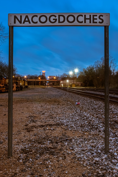Nacogdoches!, Nacogdoches TX<br /> <br /> The train yard in downtown Nacogdoches.  It started to thunder and lightning, so I had to leave before I really got this composition figured out.  On my way home I drove the most torrential downpour I've ever seen.  I couldn't see anything even with my windshield wipers blasting at full speed.  Luckily I only had a few blocks to get home and could get there going only a few miles per hour.  Our street looked like a river.  And they say we're in for even bigger storms later this week.<br /> <br /> This is a 5 exposure HDR.  One of the 5 exposures was taken at f/18, creating the starburst effect on the lights.  The other four exposures were taken at f/10.<br /> <br /> Critiques are always welcome.<br /> <br /> UPDATE: The composition that I wanted to try before the storm hit, was to compress the frame using my 135mm lens and moving a long ways back to get most of this Nacogdoches sign, some lines from the train tracks, and the Lone Star Feeds sign in the background but within the frame of the Nacogdoches sign.  Maybe I'll go back during blue hour today.<br /> <br /> Daily photo: February 19, 2013, taken February 18, 2013