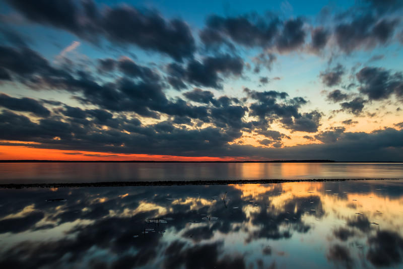 "Reflections, Lake Sam Rayburn TX  The aftermath of a <a href=""http://smu.gs/14ImA2q"">very pretty sunset</a>.  The clouds rolled in fast just before sunset and here you can see they started to dissipate soon after.  On the way to the lake that day I was telling Nini that we'd probably end up with no clouds, no sunset and head home early!  Every shoot is an adventure and that's why I always say that you never know if there is going to be a good sunset or sunrise unless you're there.  This is a single 15 second exposure.  I used a circular polarizer to increase the glare on the water, bringing out the reflection.     Critiques are always welcome.  Daily photo: February 3, 2013, taken January 25, 2013"