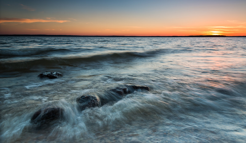 "Wavy Sunset, Lake Sam Rayburn TX  We were really surprised to find that our little beach at Lake Sam Rayburn was only about half of it's normal size due to high water.  And the lake had huge two foot waves!  It was crazy!  The beach looked totally different and lots of rocks were now in play for foreground composition.  It was a fun change of pace.  Things were looking good until about a half hour before sunset when almost all of the clouds cleared out, making the sunset a bust.  So I spent more time playing around with the dogs and taking video and I never quite got around to polishing off this composition.  If I could do it over I'd like to move back a foot and get my tripod even lower.    This is a single exposure using the two filter set up I mentioned <a href=""http://smu.gs/14ImA2q"">here</a>.  Critiques are always welcome.  Daily photo: March 5, 2013, taken March 3, 2013"