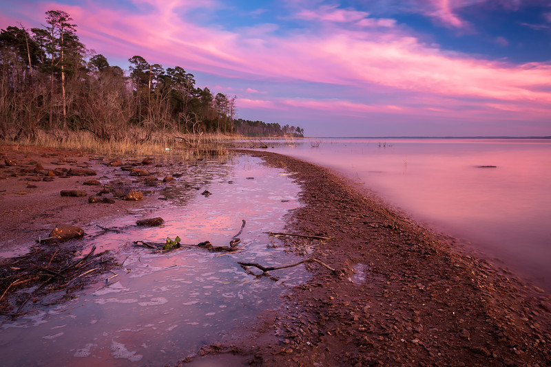 "Pink Skies after Sundown, Lake Sam Rayburn TX  This is the view to the Southeast about 10 or 15 minutes after sundown.  There was an abnormal amount of color going on in that direction and neither I nor Sarah (who was shooting with me) were set up to capture it.  We were ready to leave, but the sky had other plans.  I worked fast and got a few shots before the color faded.  The composition turned out pretty horrible, but color like this is pretty forgiving.  This is a single six second exposure.  I used a circular polarizer to create more contrast in the sky and enhance the reflection.    I'm happy to have received some constructive feedback yesterday on my portrait of Nini.  Several people mentioned found the pole on the left side of the frame distracting, and nobody came out in favor of the pole.  So I updated my post to balance out the conversation.  Check it out <a href=""http://smu.gs/15PpBPb"">here</a>.  Critiques are always welcome.  Daily photo: February 27, 2013, taken February 23, 2013"