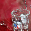 5/7/08<br /> Pouring near-boiling water into a God Bless America shotglass. It took quite a bit of practice to time it right, but I think the splashing water looks pretty cool, and it's definitely more interesting with the steam. Still, a very random photo.