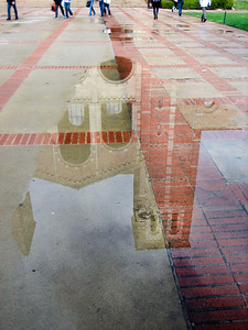 2/9/09 Still more rain in LA, hooray for the water! This was taken shortly after noon when the rain had stopped, but puddles hadn't dried up yet. This is a reflection of Royce Hall. I like how I was able to get only the students' legs in the shot. I played around to get better clarity on the reflection, but I ended up backing off of many of my edits so it looked more natural. I tend to overdo the contrast...