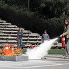 2/26/09<br /> Today at work I attended a fire extinguisher training and we all got to put out a fire, it was fun! This is my fellow employee Monique, with other coworkers looking on (there were about 20 of us total). If you think she's missing the flame, don't worry, she got it out very quickly!<br /> I took many, many photos, most of which were throwaways, but I like this one because it shows the propellant (basically baking soda) and the flame at the same time. The heat from the flame makes some neat ripples in the air, too. I slightly desaturated this photo except for orange and red. <br /> If you're curious, the metal container is filled with water, and the hose attached is propane, which bubbles up to fuel the flame. Our fire fighter instructor relit the flame after every person with a flare attached to a long handle.