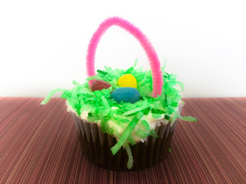 """<span id=""""date"""">_03/29/10_</span> <span id=""""title"""">Easter Basket</span> Ah, the joy of a surprise cupcake! A coworker of mine shared these fun Easter basket cupcakes while we did the delightful task of moving furniture. The pattern comes from a chair that I put up against a white wall. I edited in Lightroom with the goal of making the cupcake pop out.  <a href=""""http://www.jawsnap.net/gallery/7157835_BfJPF#501715407_tQASE"""">[last year]</a> <em>currently my most popular photo!</em>"""