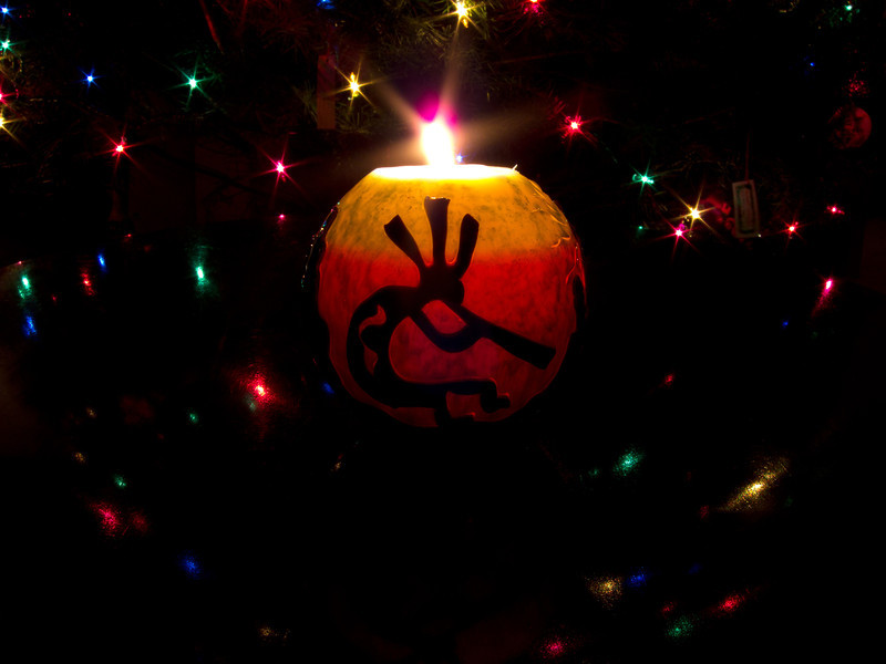 """<span id=""""date"""">_12/25/10_</span> <span id=""""title"""">Kokopelli Candle</span> Merry Christmas! And thanks to all the nice comments on yesterday's photo! My wife and I picked up this candle from the <a href=""""http://www.globalcandlegallery.com/"""">Sedona Candle Company</a> last week. The store is really neat and the employees are cool, I highly recommend stopping by to see them in action. For this shot, I placed the lit candle on a shiny wood table that was next to my parents' Christmas tree. I set my S95 to manual mode at ISO 80, f/8 (the lowest and smallest) and played with the shutter speed to get the right exposure, which ended up being 2.5 seconds.  By the way, did I mention you can get a free shirt just for <a href=""""http://products.wolframalpha.com/holidayspikey/gallery/view.jsp?id=504"""">voting for me</a>?  <a href=""""http://www.jawsnap.net/Daily/year2/7157835_BfJPF#749706929_dhxr2"""">[last year]</a> <em>swirly...</em>"""