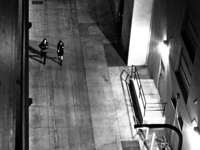 __01/29/11__ Walking in Black These two women were photographed while walking down an alley in Santa Monica. My position was on level 8 of a parking garage. We had just watched True Grit. I liked it.  You may have noticed that this photo is a bit gritty. Truly, it's because of the ISO noise.  [last year]
