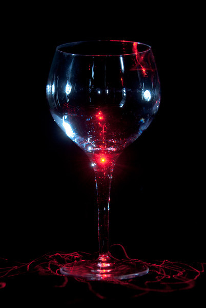 """<span id=""""date"""">_11/29/10_</span> <span id=""""title"""">Laser Wine</span> Today's photo was inspired by a laser pointer that I brought home from work. I wiggled the laser pointer around on the glass - mostly from overhead - for 30 seconds. At the end, my flash went off, which was placed to the right of the glass and used a snoot to direct the light and not light up the background. I changed the white balance in Lightroom to give a blueish hue to the glass, but otherwise it's been minimally edited.  <a href=""""http://www.jawsnap.net/Daily/year2/7157835_BfJPF#727257388_KzsjZ"""">[last year]</a>"""