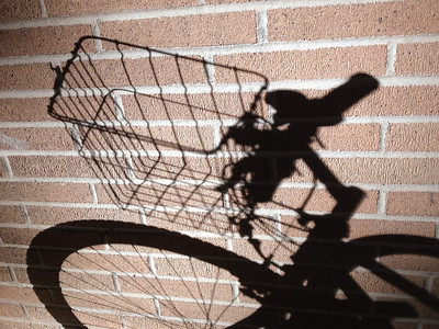 __01/27/12__ Brick Bike Basket Simple shot of a bike shadow that caught my eye. I took a lot of photos with my phone today, mostly of an open house that I helped put on. It was a lot of work, but a lot of fun and very rewarding once it was over! It helped to grab a drink or two (or five) after work with coworkers.  Fun fact: I'm eating some of yesterday's photo while I type this!  [last year] I miss the botanical gardens...