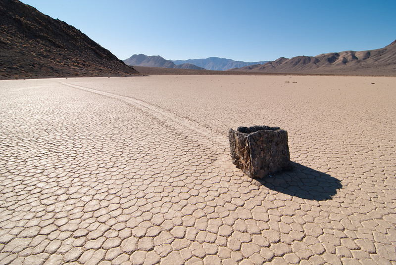 """<span id=""""date"""">_11/25/11_</span> <span id=""""title"""">Rock in Motion</span> <em>Death Valley, Day 3</em> If you've heard of it before, you probably recognize this as a photo of the Racetrack. If you haven't, let me tell ya: The Racetrack is a mud playa in Death Valley National Park, where the rocks move. No one has ever seen it happen and no one has been able to prove how it happens, but the evidence is right there - huge rocks with long mud trails behind them. The theory is that when the playa gets wet, it gets slippery enough that high winds are able to push the rocks around. It's a truly amazing place and I enjoyed every minute that we spent there. The road to it is not easy. You need an SUV at the very least - a lot of people rent Jeeps to make the trip. It's a long trip, too - took us most of the day, and we left pretty darn early.  Here's what the National Park Service Sign says: <em>""""The moving rocks are something of a mystery. Scientists theorize that when this ancient lake bed - or playa - gets wet, it becomes so slippery that winds can move rocks weighing 100 pounds or more. Others suggest that winds move the rocks only when ice helps them raft along a temporary lake surface."""" </em> <a href=""""http://www.jawsnap.net/Travel/DeathValley2011/20327429_xbqMPq"""">More Death Valley Photos</a>  <a href=""""http://www.jawsnap.net/Daily/year3/11272102_ACXDJ#1104920556_ezUMh"""">[last year]</a> <em>huh, a year ago we walked across lava flats...<em>"""